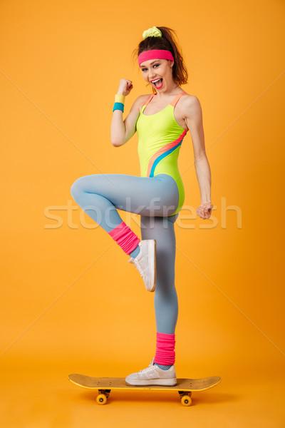Teljes alakos mosolyog fiatal nő atléta áll gördeszka Stock fotó © deandrobot