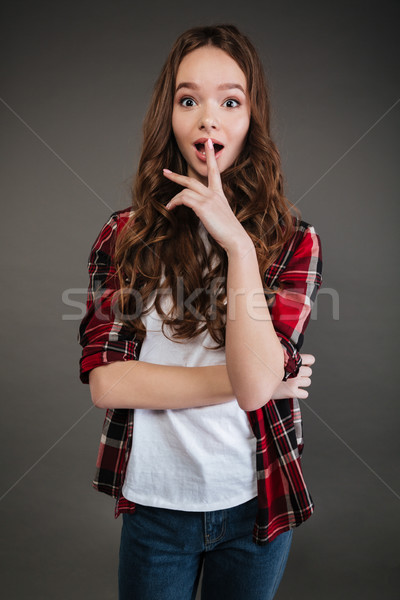 Surprised pretty young woman standing with opened mouth Stock photo © deandrobot