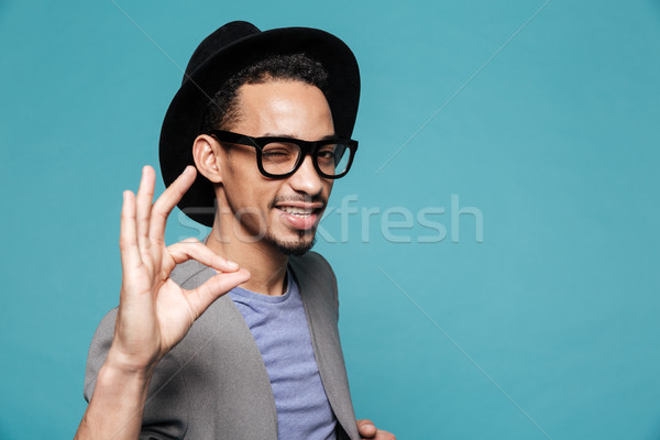 Portrait of a young afro american man in hat winking Stock photo © deandrobot
