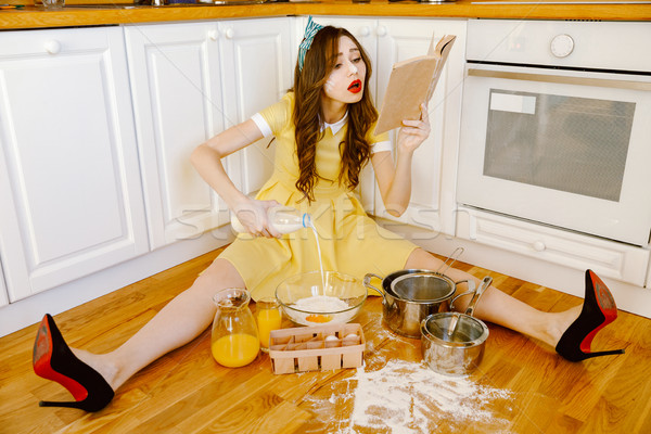 Stock photo: Concentrated young pin-up woman cooking and reading recipe