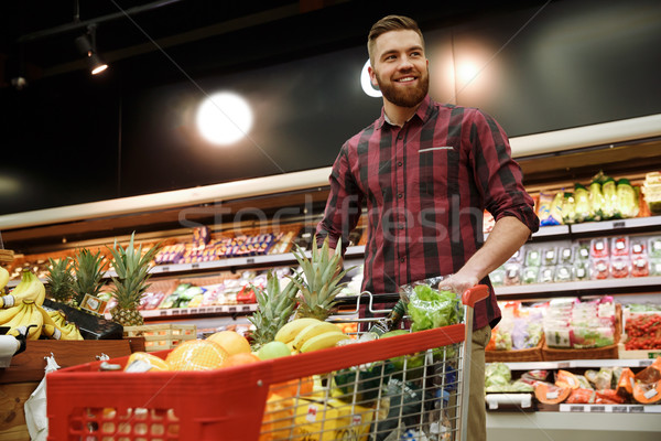 Cheerful man with shopping trolley choosing fruits Stock photo © deandrobot