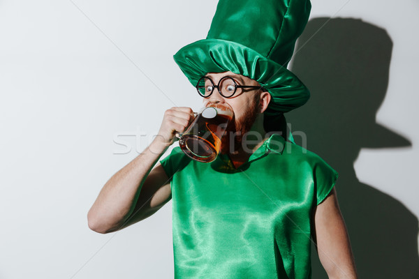 Funny drunk man in st.patriks costume drinking beer Stock photo © deandrobot