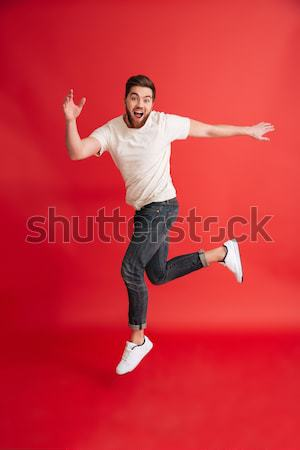 Vertical image of funny man playing on imaginary guitar Stock photo © deandrobot