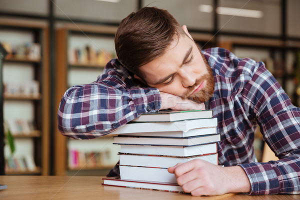 Tired young man holding his head on the book stack Stock photo © deandrobot