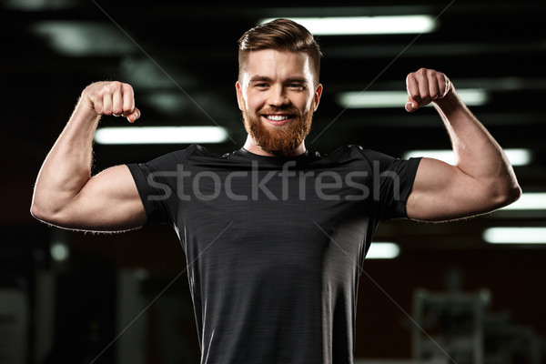 Happy sports man showing his biceps. Stock photo © deandrobot