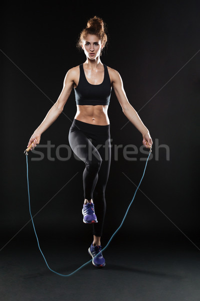 Full length image of fitness woman jumping with jumping-rope Stock photo © deandrobot