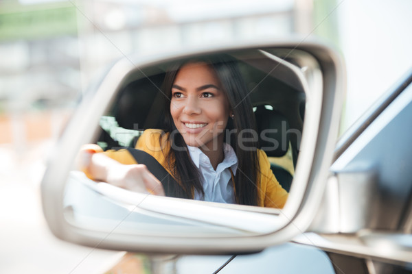 Smiling business woman in side view car mirror Stock photo © deandrobot