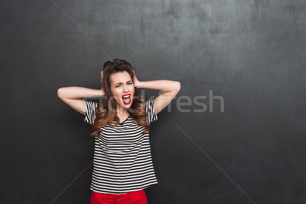 Screaming woman covering her ears Stock photo © deandrobot