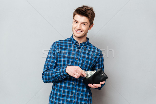 Happy man standing over grey wall holding purse with money. Stock photo © deandrobot