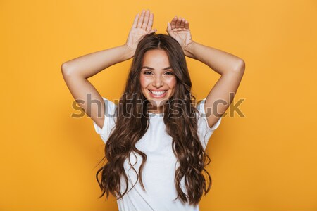 Girl in beachwear posing and keeping hands on her hat Stock photo © deandrobot