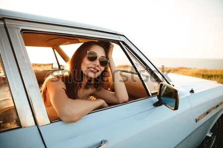 Smiling young woman in sunglasses leaning on a window Stock photo © deandrobot