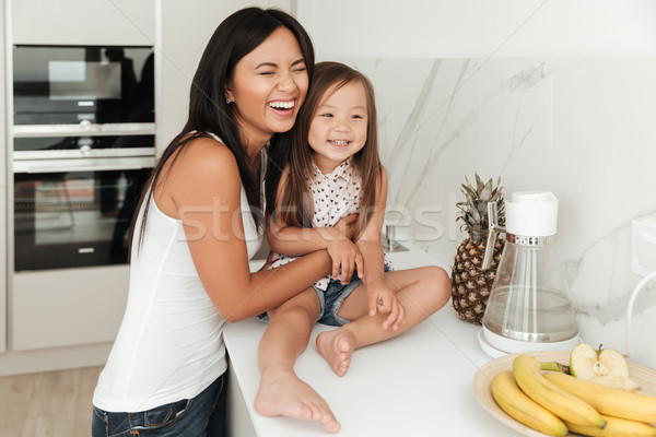 Young pretty asian woman and her daughter laughing Stock photo © deandrobot