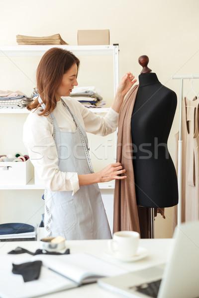 Woman measuring fabric on black dummy Stock photo © deandrobot