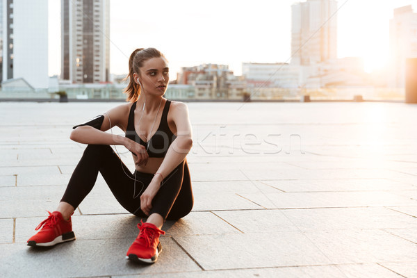 Young sportswoman resting while sitting outdoors Stock photo © deandrobot