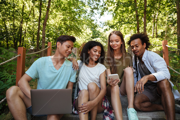 Four friends sitting on stairs in forest with laptop Stock photo © deandrobot