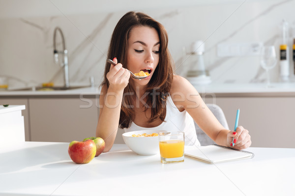 Stock photo: Casual young woman eating corn flakes cereal for breakfast