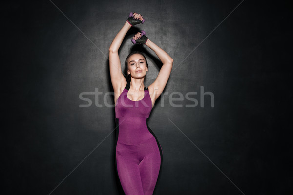 Strong healthy woman raising hands while standing over black background Stock photo © deandrobot