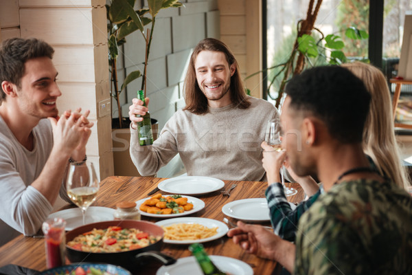 Group of people drinking beer and wine at the dinner Stock photo © deandrobot