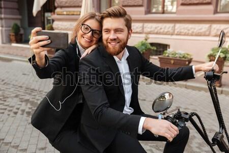 Cheerful stylish couple satting on modern motorbike outdoors Stock photo © deandrobot