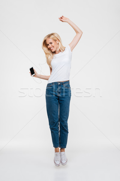 Full length portrait of a young casual blonde woman Stock photo © deandrobot