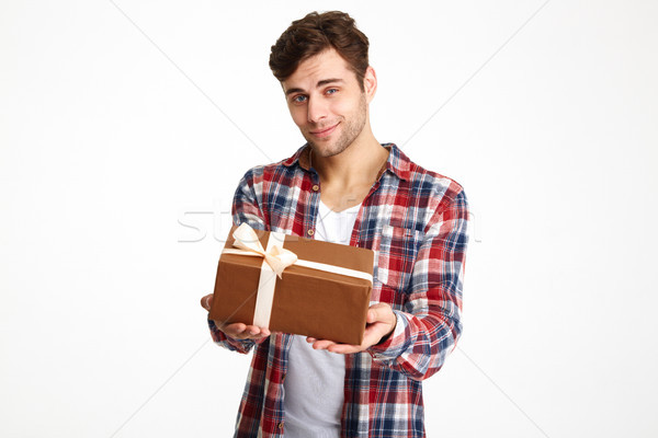 Portrait of an attractive casual man holding a present box Stock photo © deandrobot