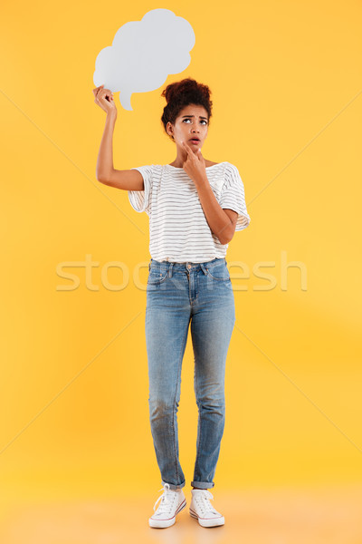 Full length image of displeased pensive african woman looking up Stock photo © deandrobot