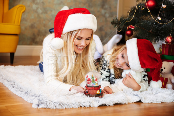 Cheerful woman and little girl in Santa's hat playing with snow  Stock photo © deandrobot