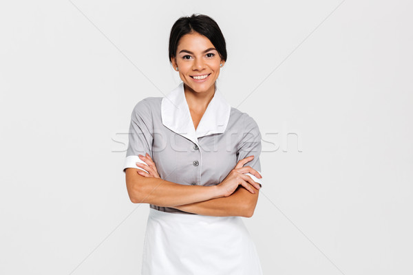 Close-up portrait of young smiling housekeeper in uniform standi Stock photo © deandrobot
