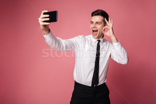 Derűs fiatal üzletember mutat oké kézmozdulat Stock fotó © deandrobot