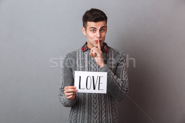 Young man holding paper with love text showing silence gesture. Stock photo © deandrobot
