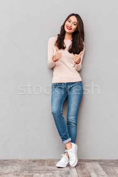 Full-length photo of beautiful woman with long brown hair showin Stock photo © deandrobot