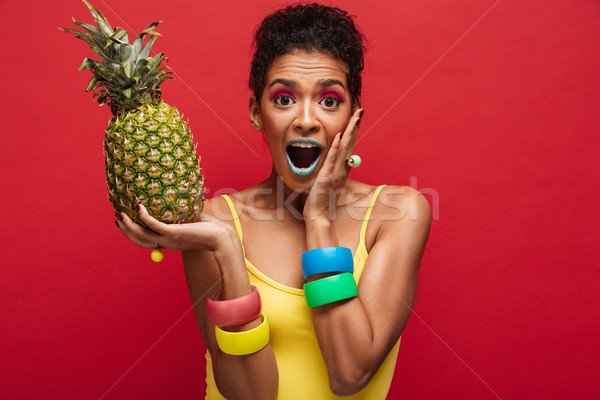 Mulatto woman in colorful outfit being excited while holding in  Stock photo © deandrobot