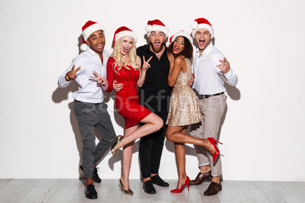 Portrait of a cheery happy multiracial group of friends celebrating Stock photo © deandrobot