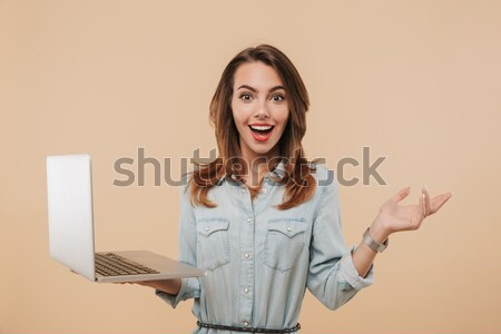 Happy exited attractive girl in warm clothes holding laptop comp Stock photo © deandrobot