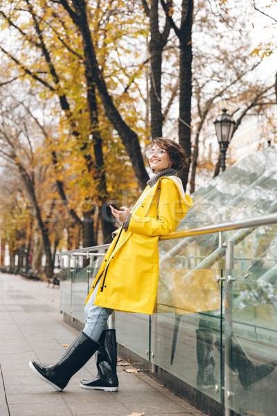 Verbazingwekkend jonge vrouw regenjas foto lopen buitenshuis Stockfoto © deandrobot