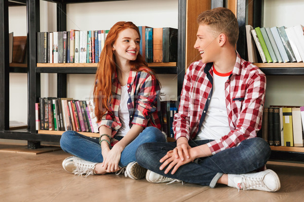 Smiling teenage couple sitting on a floor at the bookshelf Stock photo © deandrobot