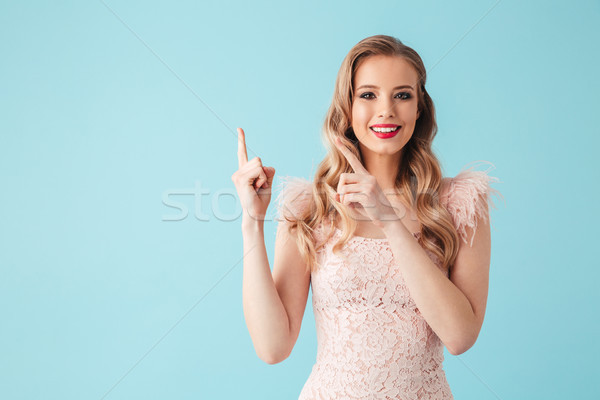 Happy blonde woman in dress pointing on copyspace Stock photo © deandrobot