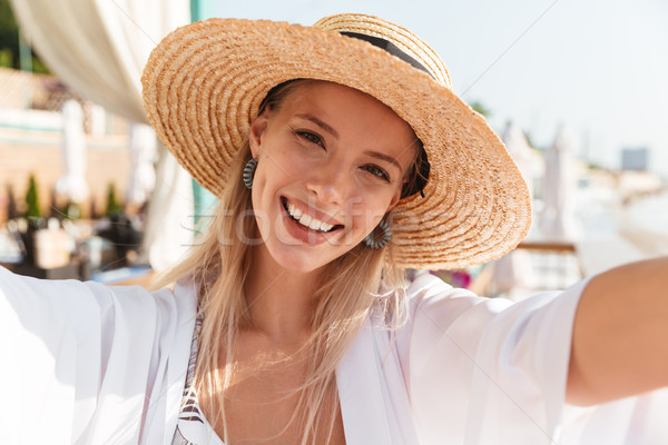 Photo closeup of beautiful young woman 20s in straw hat and swim Stock photo © deandrobot