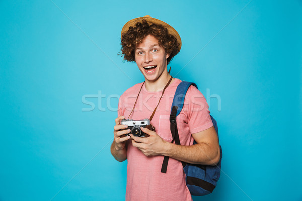 Image of smiling tourist guy 18-20 with curly hair wearing backp Stock photo © deandrobot