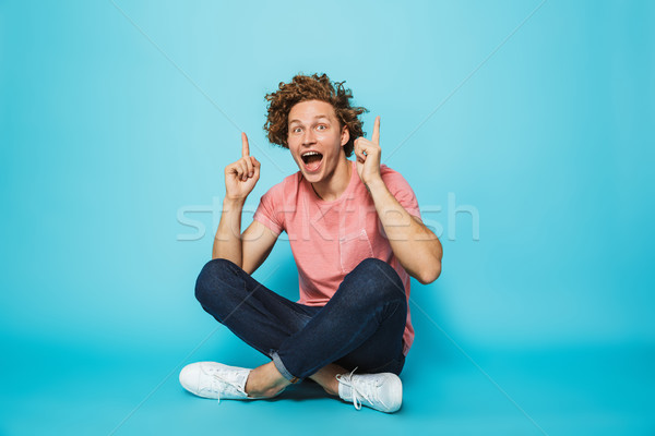 Portrait of a cheerful young curly haired man pointing up Stock photo © deandrobot