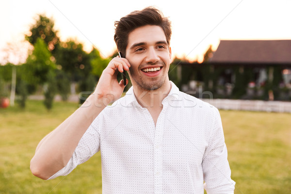 Image of joyful young man 25-30 wearing white shirt smiling, and Stock photo © deandrobot