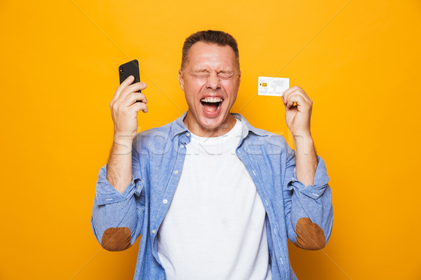 Portrait of a happy middle aged man using mobile phone Stock photo © deandrobot