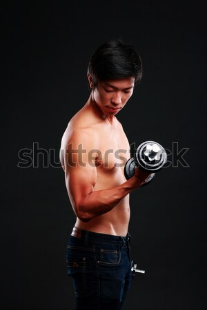 Muscular man lifting barbell over black background Stock photo © deandrobot