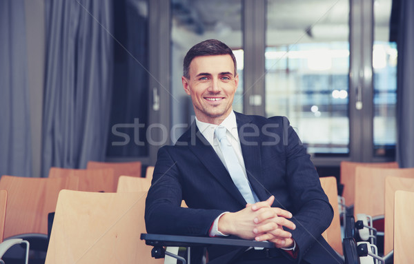 Smiling businessman sitting at conference hall Stock photo © deandrobot