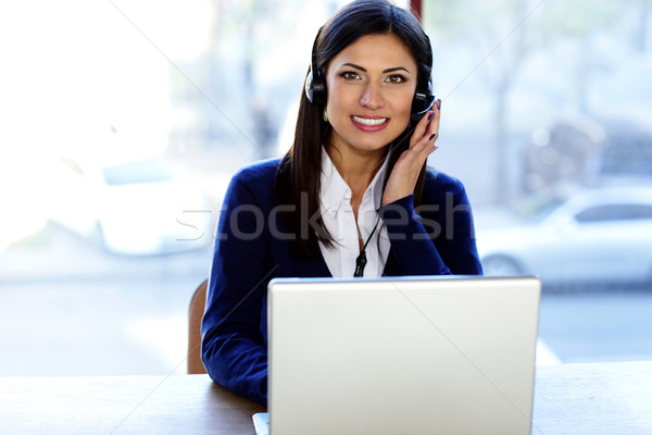 Happy beautiful call-center assistant at the desk Stock photo © deandrobot
