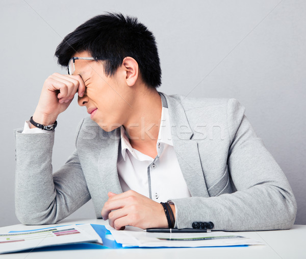 Tired businessman sitting at the table Stock photo © deandrobot