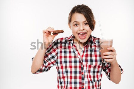 Young casual man biting money over gray background Stock photo © deandrobot
