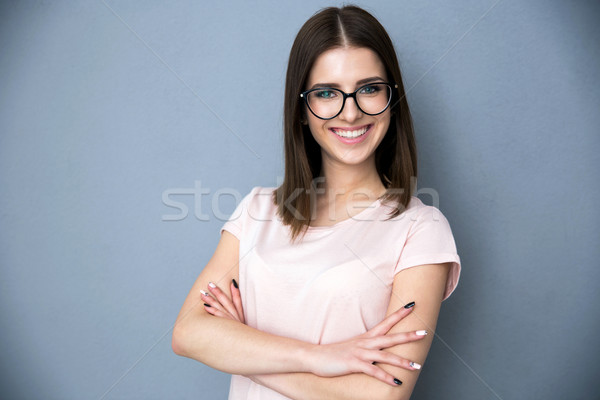 Portrait of a smiling young woman with arms folded Stock photo © deandrobot