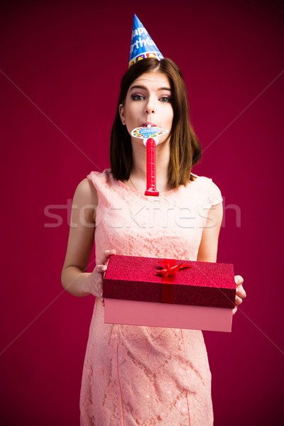 Woman blowing in whistle and holding gift box Stock photo © deandrobot