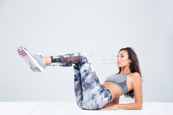 Portrait of a sports woman doing abs exercises Stock photo © deandrobot